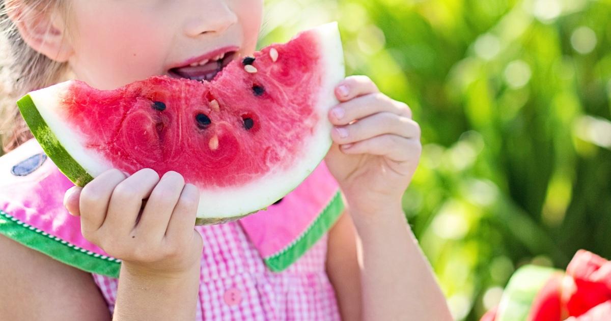Bambina mangia anguria. Estate: bambini e alimentazione.
